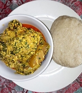 Egusi soup being served with cassava flour (Alebo)