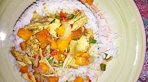 A plate of rice served with shredded chicken sauce