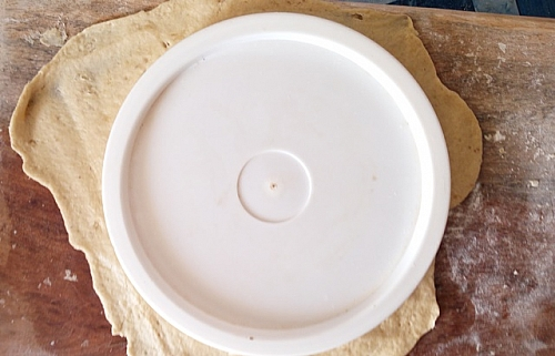 Place any round plate or surface over rolled out tortilla to cut it into round shell