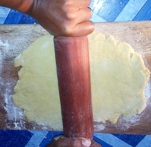 Process of rolling out pie crust dough into a flat pastry.