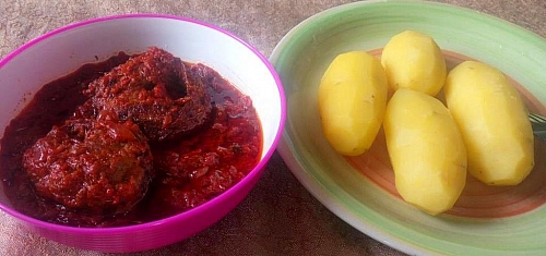 Tomato fish stew is served with boiled Irish potatoes