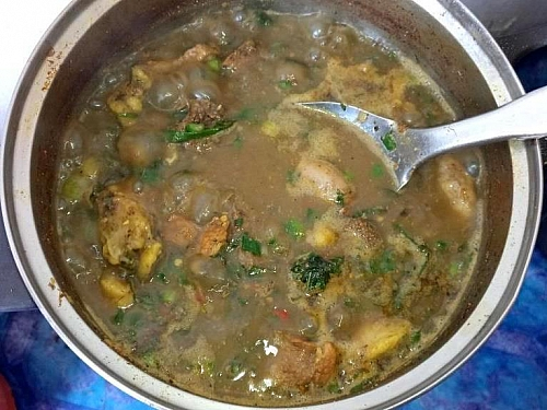 Scent leaf and spring onions are being added to assorted pepper soup