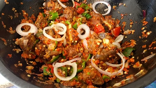 Garnish your spicy peppered goat meat with onion rings and it is ready