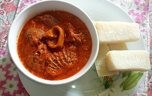 Serving assorted meat stew with boiled yam