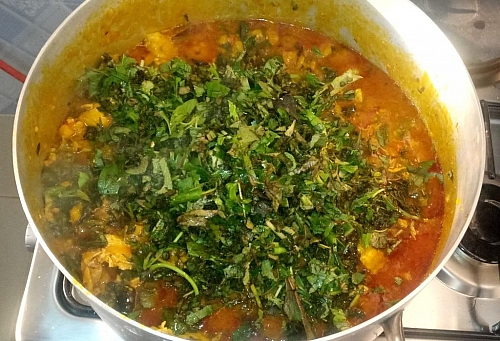 Adding of scent leaves ( basil) to garnish ekpang nkukwo