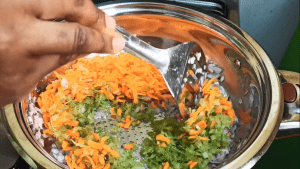 celery and carrots being stir fried while making meat sauce for spaghetti bolognese