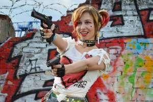 Actress depicting a comic character 'Harley Quinn' wielding 2 handguns gleefully
