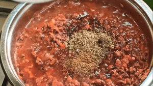 Oregano, black pepper, thyme, cumin used as seasonings in meat sauce for spaghetti