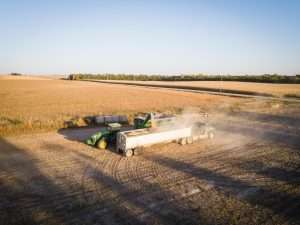Agronomy in Agriculture illustrated with combined harvester loading harvested grain into articulated vehicle with grain fields in the background