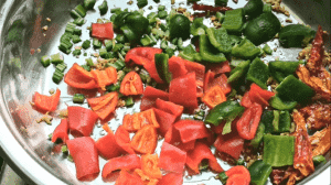 Next, add 2 tbsp of chopped celery and chopped capsicums; stir fry for 2 minutes until the peppers are soft.