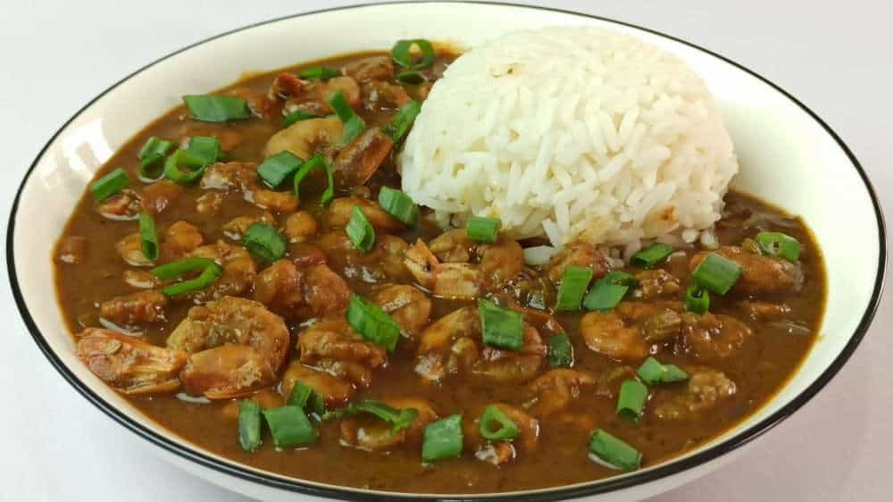 Etouffee served with rice and garnished with chopped spring onions.