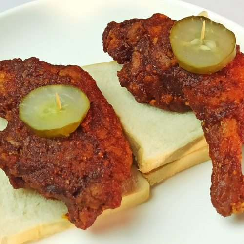 Nashville Hot Chicken served with pickled cucumber over sliced of bread
